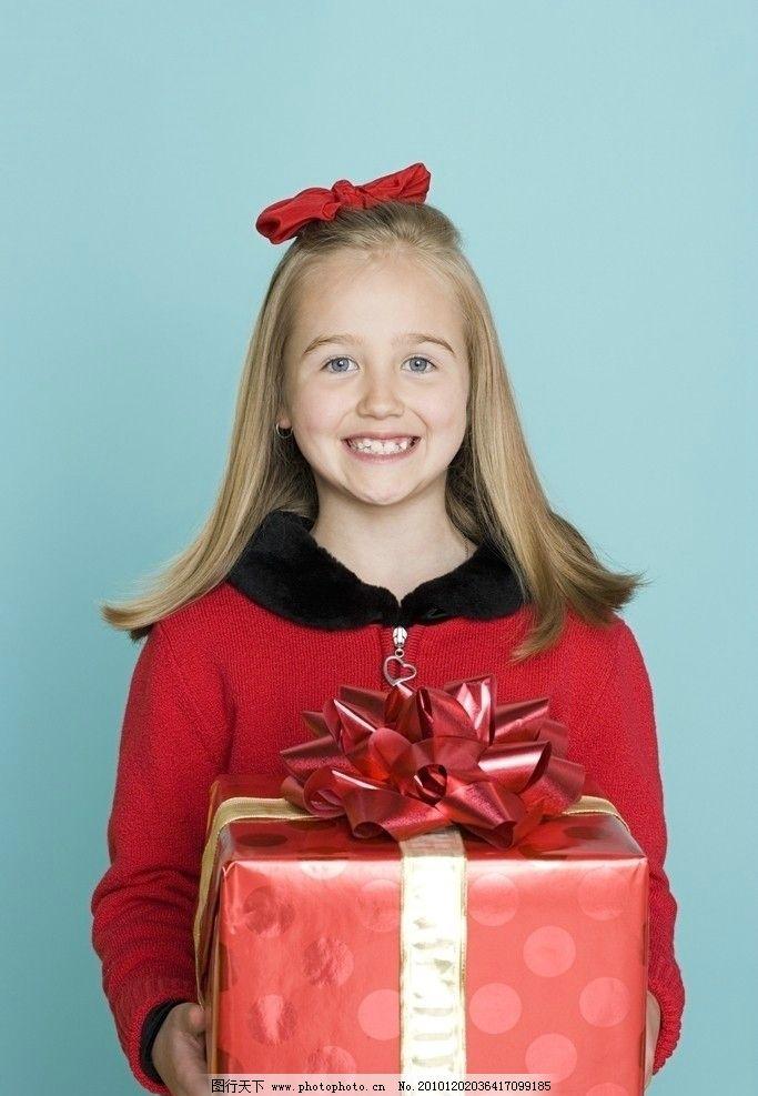 手捧礼盒的微笑小女孩图片